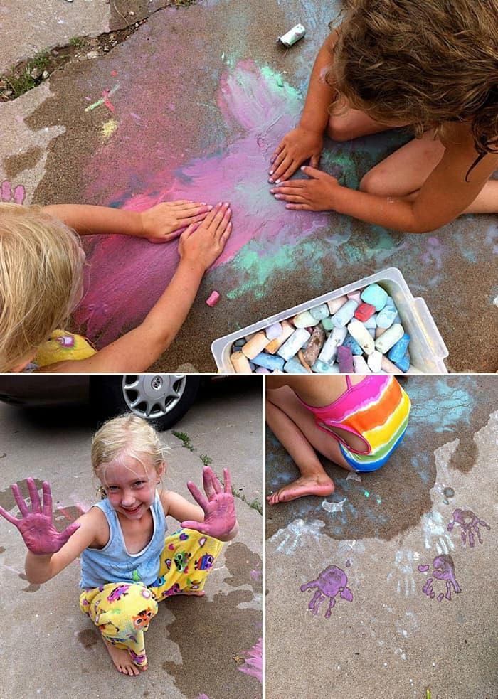 Kids showcasing their chalk art ideas, but using wet hands and sidewalk chalk to create painted chalk handprints.
