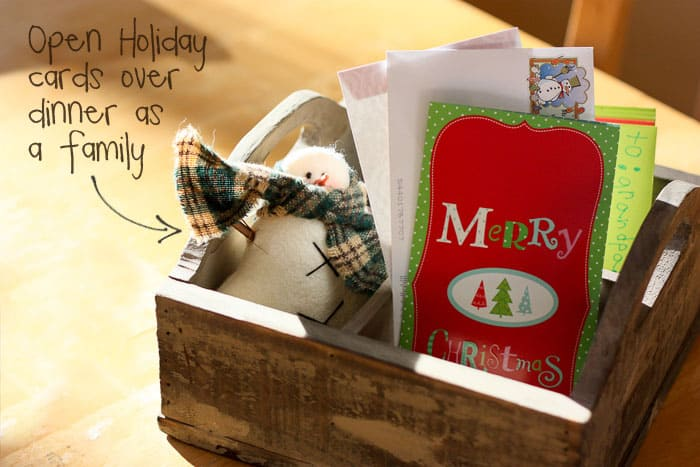 Stack all the holiday cards from the mail in the center of the kitchen table each day. Then take turns opening them during dinner.