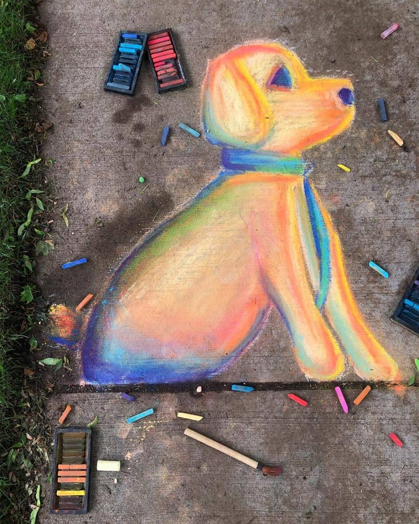 Sidwalk chalk art showcasing a puppy, plus chalk art supplies.