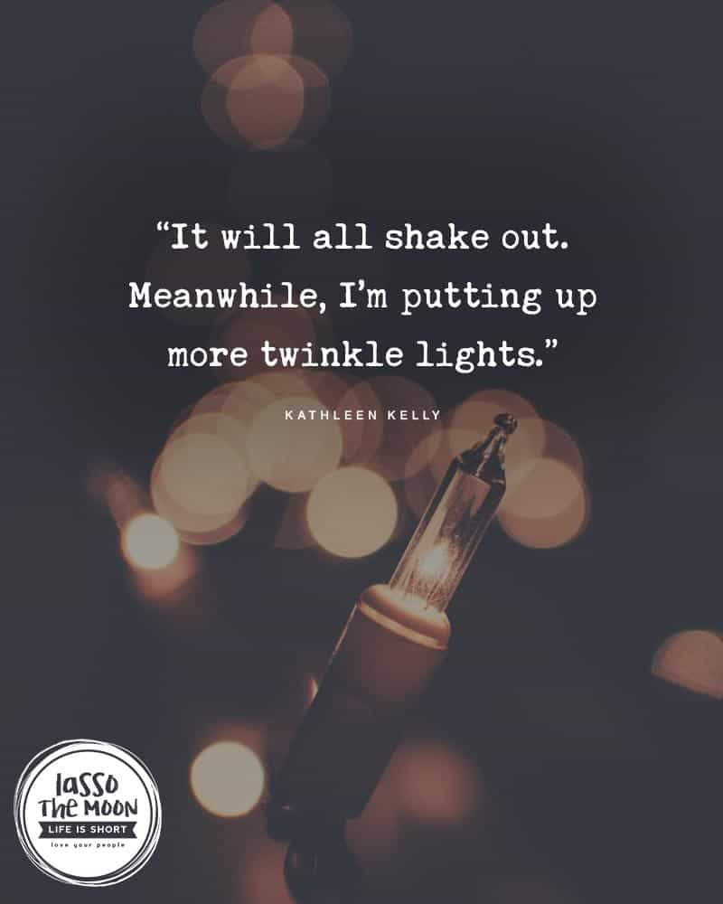 "A close-up of a Christmas tree light with a quote on top reading, ""It will all shake out. Meanwhile, I'm putting up more twinkle lights."""