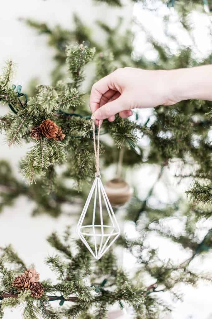 A woman hanging a minimalistic Christmas tree decoration on a rustic pine tree.