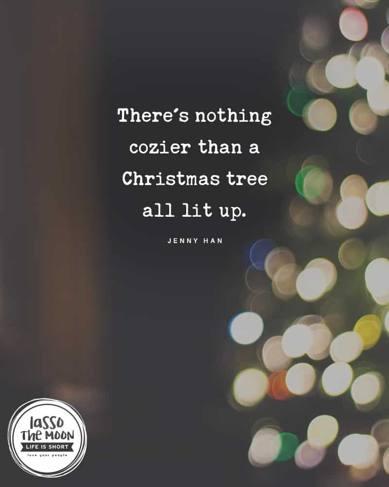 "A blurred photo of Christmas tree lights bokeh with the followig quote written overtop, ""There's nothing cozier than a Christmas tree all lit up."""