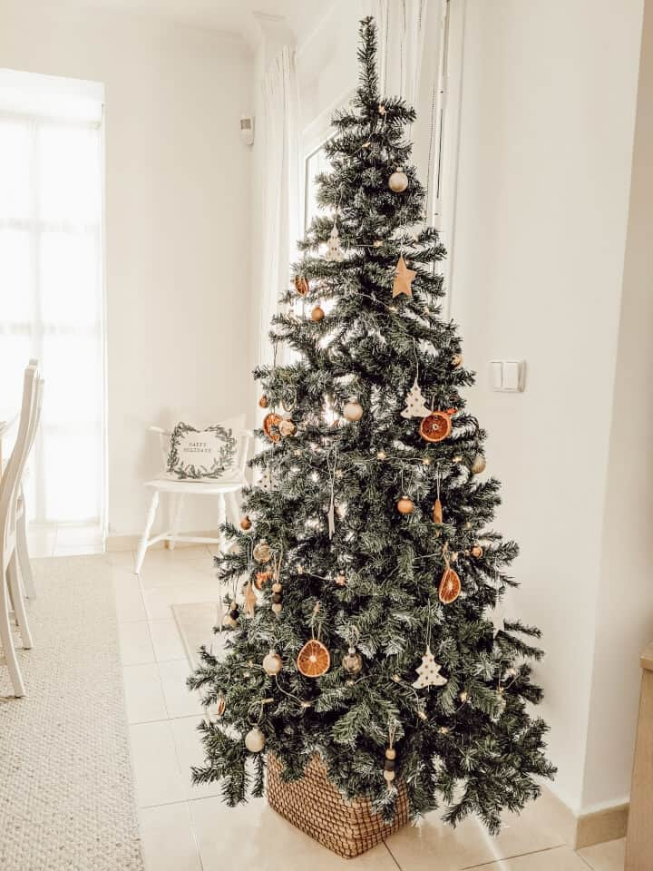 A natural Christmas tree decorations like pinecones, dried orange slices, and wood oranments.