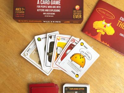 The card game Exploding Kittens Game layed out on a table with the cards displayed.