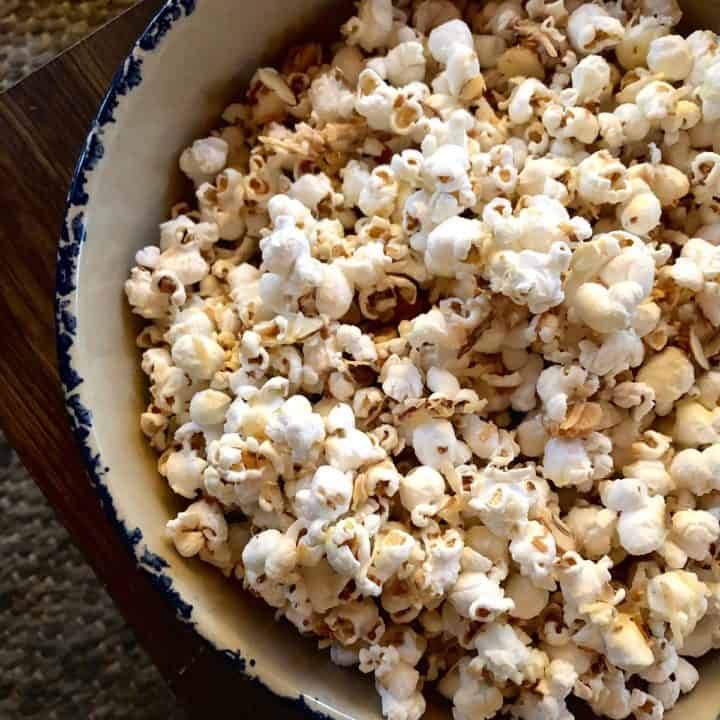 A bowl of popcorn covered in white chocolate.