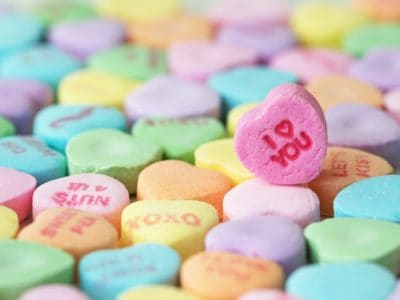 "Valentine's Day candy hearts with one highlighted saying ""I love you"""